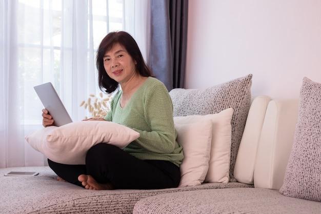 Menina bonita em casa que usa o portátil no sofá, mulher asiática idosa.