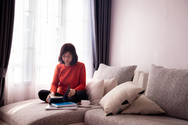 Menina bonita em casa sentado no sofá, lendo um livro.