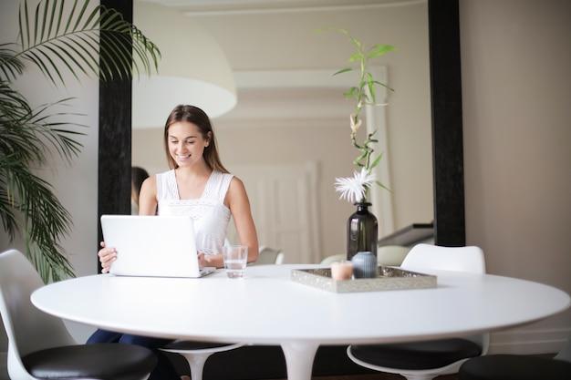 Menina bonita em casa trabalhando em um laptop