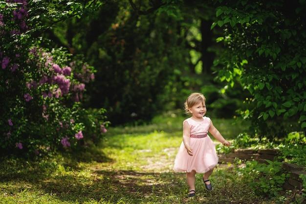 Menina bonita em dia ensolarado. menina de cabelos loiros no vestido rosa, sorrindo entre as árvores florescendo.