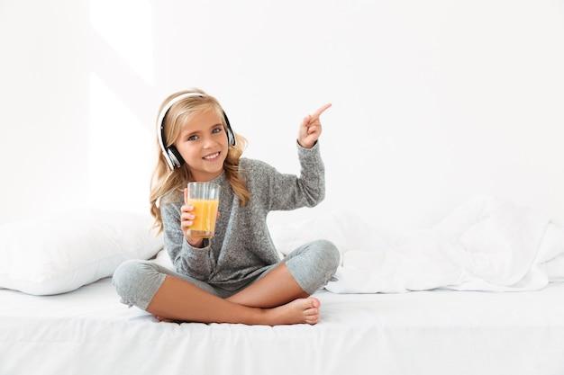 Menina bonita em fones de ouvido, segurando o copo de suco de laranja, apontando com o dedo, enquanto está sentado na cama