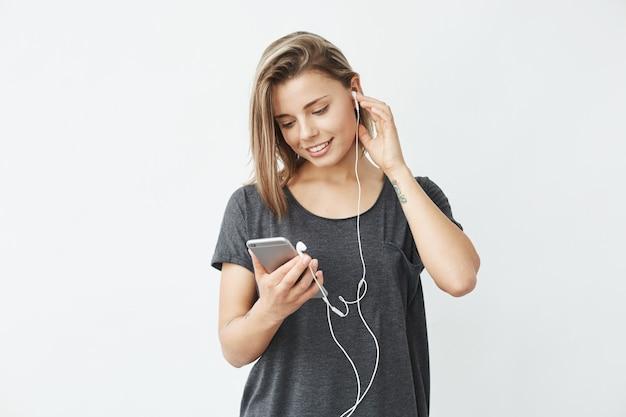 Menina bonita em fones de ouvido, sorrindo, olhando para a tela do telefone.