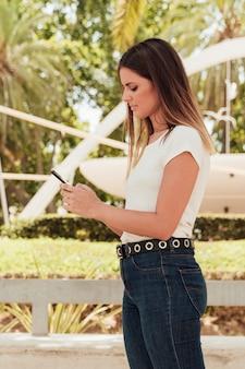 Menina bonita em jeans, verificando o smartphone