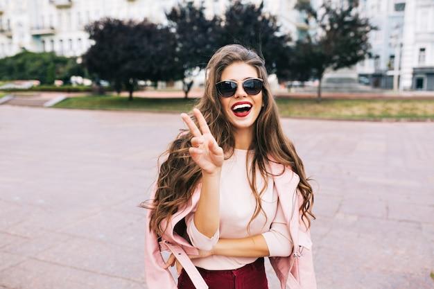 Menina bonita em óculos de sol com penteado longo, se divertindo na cidade. ela usa lops vinosos, tem um grande sorriso branco como a neve.