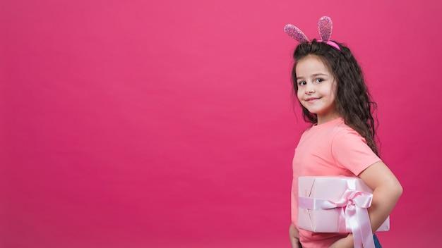 Menina bonita em orelhas de coelho com caixa de presente