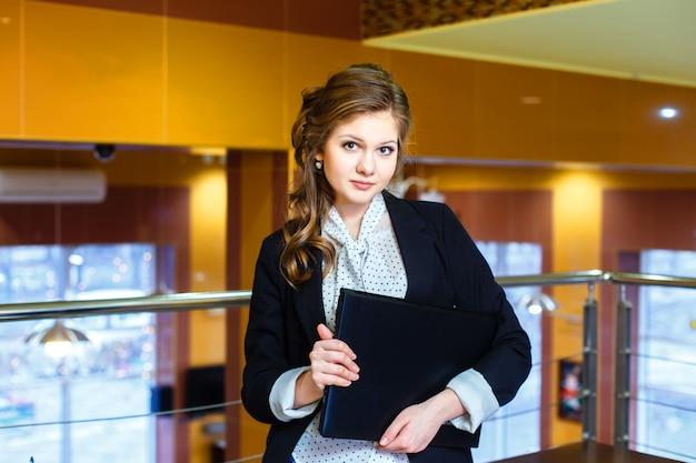 Menina bonita em pé em um escritório e segurando um laptop