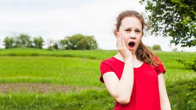 Menina bonita em pé no parque, tendo dor de dente
