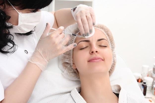 Menina bonita em procedimento de rejuvenescimento na clínica de beleza
