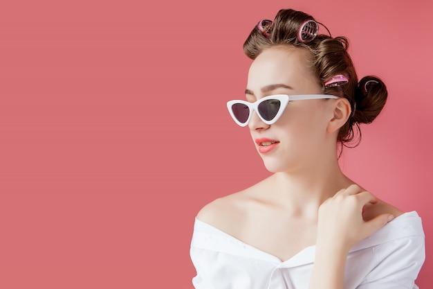 Menina bonita em rolos de cabelo em fundo rosa
