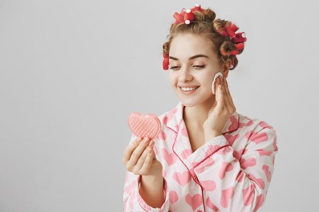 Menina bonita em roupa de dormir e bobes de cabelo, olhando no espelho e removendo a maquiagem em um bloco de algodão