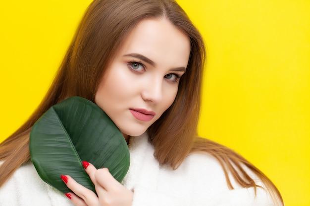 Menina bonita em roupão e pele bonita, segurando a folha verde em um amarelo