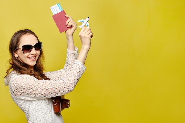 Menina bonita em roupas casuais com passaporte, passagens aéreas de óculos e segurando um modelo de avião.