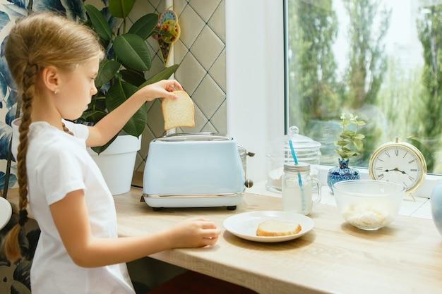 Menina bonita em sua cozinha de manhã preparando o café da manhã
