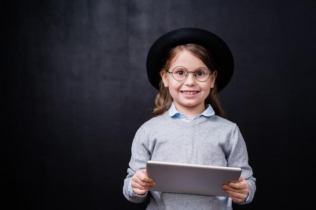 Menina bonita em trajes casuais elegantes e óculos usando o touchpad contra o espaço preto