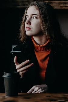 Menina bonita em um café com um telefone