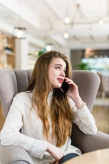 Menina bonita em um café falando em um celular