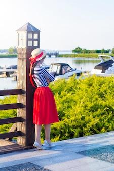 Menina bonita em um chapéu de palha no cais perto dos iate e dos barcos do mar.