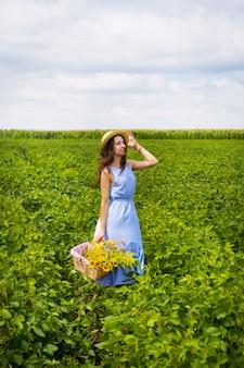 Menina bonita em um chapéu e placa azul está de pé em um campo verde