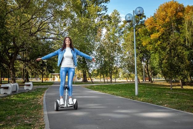 Menina bonita em um hoverboard branco no parque