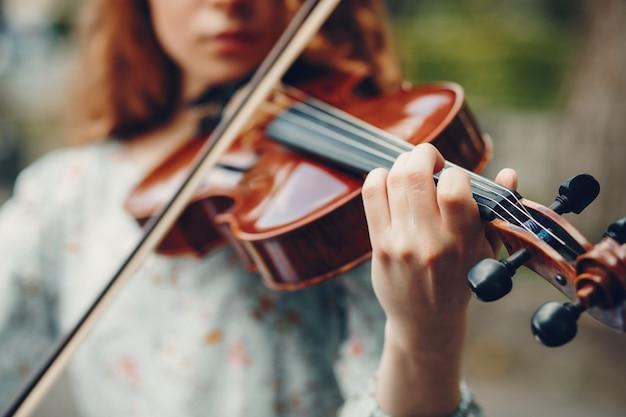 Menina bonita em um parque de verão com um violino
