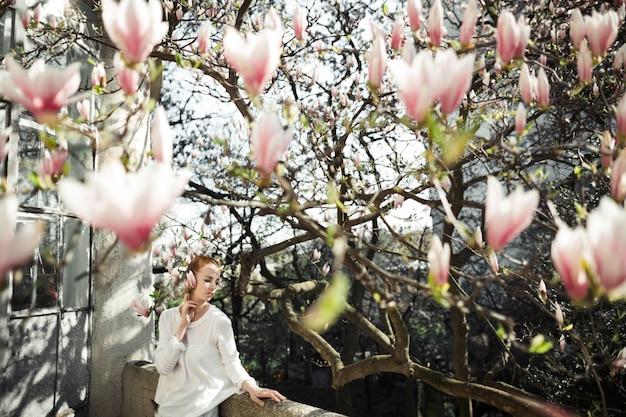 Menina bonita em um photoshoot de primavera com magnólia