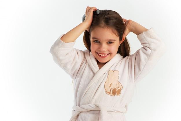 Menina bonita em um roupão de banho, pentear o cabelo