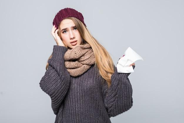 Menina bonita em um suéter cinza está resfriado e teve dor de cabeça de gripe em cinza