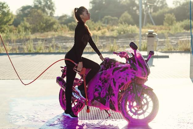 Menina bonita em um terno preto sedutor fica perto da motocicleta na lavagem de carros self-service ao nascer do sol.