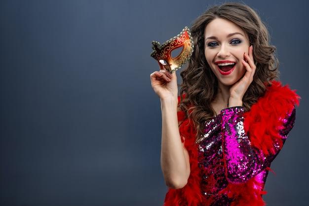 Menina bonita em um vestido brilhante e uma boa em volta do pescoço está segurando uma máscara de carnaval de prazer
