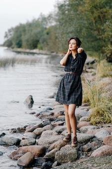Menina bonita em um vestido xadrez está de pé à beira-mar