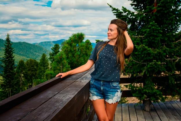 Menina bonita em uma bela paisagem montanhosa no verão