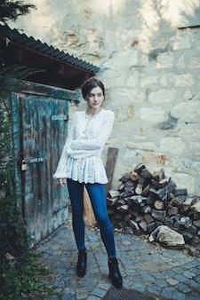 Menina bonita em uma blusa de renda branca e jeans perto da casa do fazendeiro