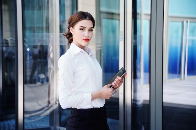 Menina bonita em uma camisa branca no fundo de um prédio de escritórios