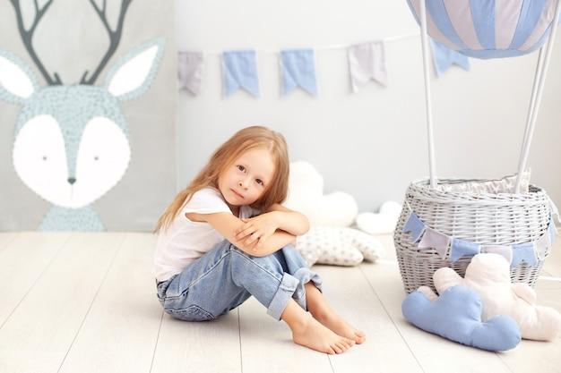 Menina bonita em uma camiseta branca e calça jeans senta-se na parede de um balão decorativo. a criança brinca no quarto das crianças. o conceito de infância, viajar. decoração do feriado de aniversário