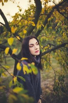 Menina bonita em uma camisola em um parque de outono