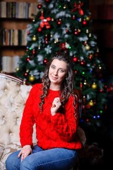 Menina bonita em uma camisola vermelha perto da árvore de natal.