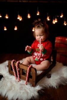 Menina bonita em uma fantasia de natal vermelha com guirlandas retrô senta-se em uma pele
