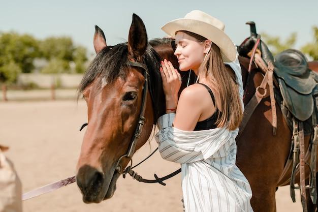 Menina bonita em uma fazenda abraça seu cavalo