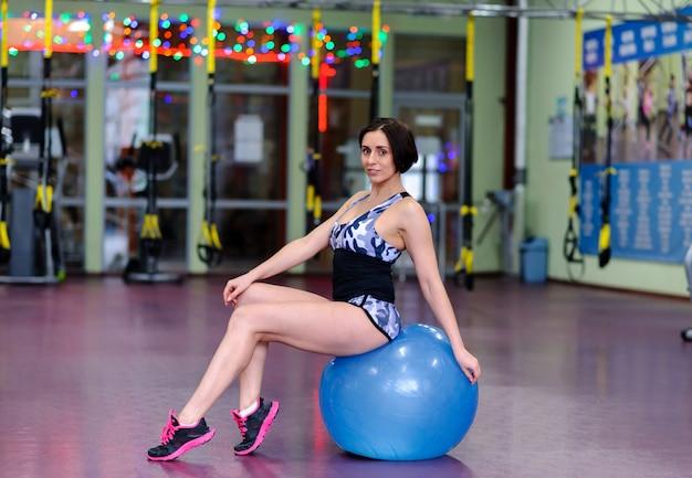 Menina bonita em uma fitball no ginásio.