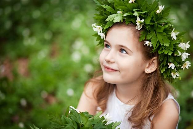 Menina bonita em uma madeira branca do vestido na primavera.