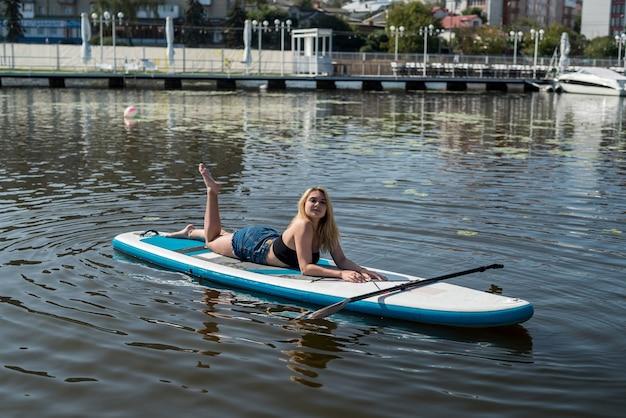 Menina bonita em uma prancha de remo no lago da cidade. estilo de vida de verão
