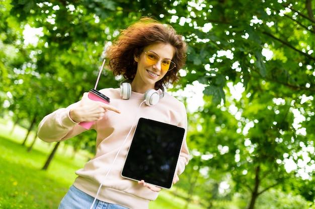 Menina bonita encantadora com um tablet com um layout no meio de um parque verde de árvores
