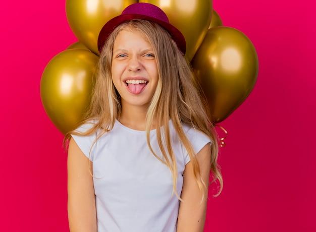 Menina bonita engraçada com chapéu de férias com um monte de balões feliz e animada