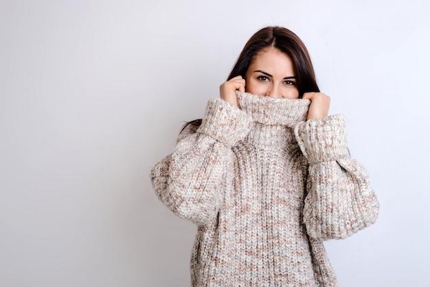 Menina bonita esconde o rosto em uma camisola.