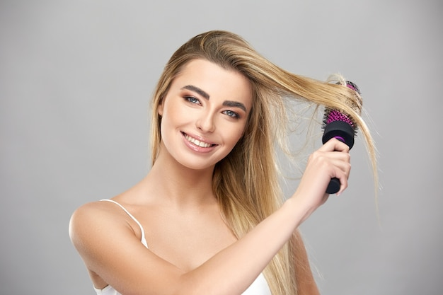 Menina bonita escovando cabelo isolado na parede cinza, tratamento capilar feminino e conceito de beleza