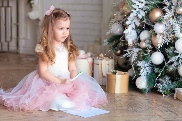 Menina bonita escrevendo carta para o papai noel na véspera de ano novo. criança está pensando debaixo da árvore de natal.