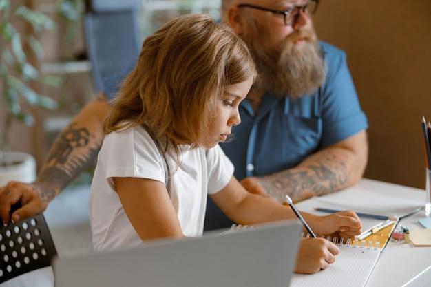 Menina bonita escrevendo no caderno sentada no laptop nera fazendo a lição de casa com o papai em casa