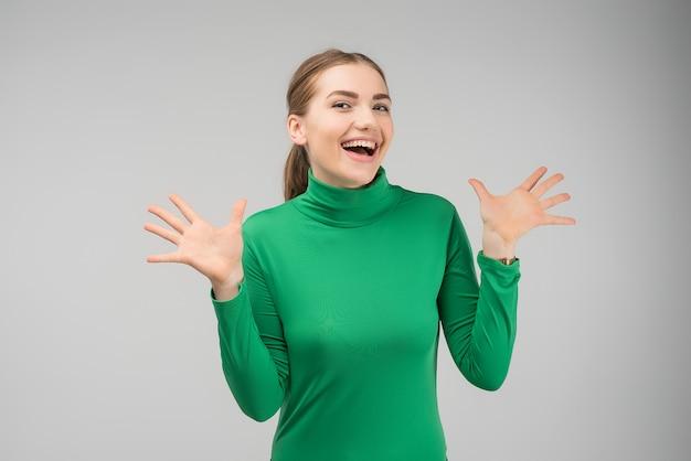 Menina bonita espantada exclama e gestos ativamente, expressa sua grande surpresa