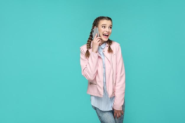 Menina bonita espantada feliz em estilo casual, cabelos trançados, em pé e falando com um telefone móvel inteligente e desviando o olhar com cara de surpresa, estúdio interno tiro isolado em fundo azul ou verde