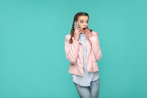 Menina bonita espantada no estilo casual, cabelos trançados, em pé e falando no telefone móvel inteligente e desviando o olhar com o rosto em choque, estúdio interno tiro isolado em fundo azul ou verde